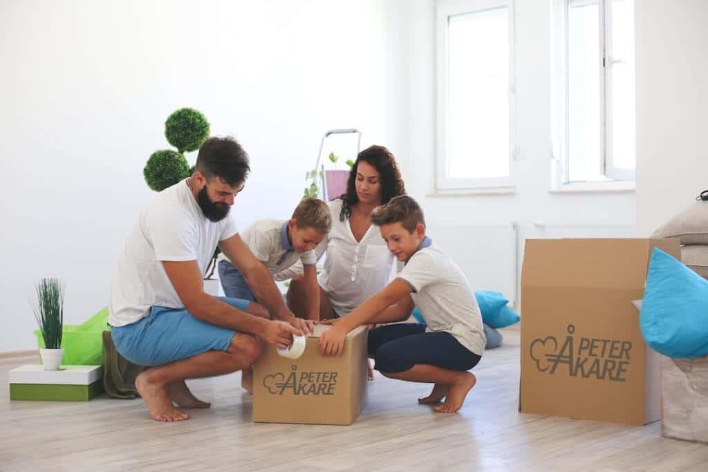 Familj som packar i saker i flyttkartonger från Peter Åkare AB