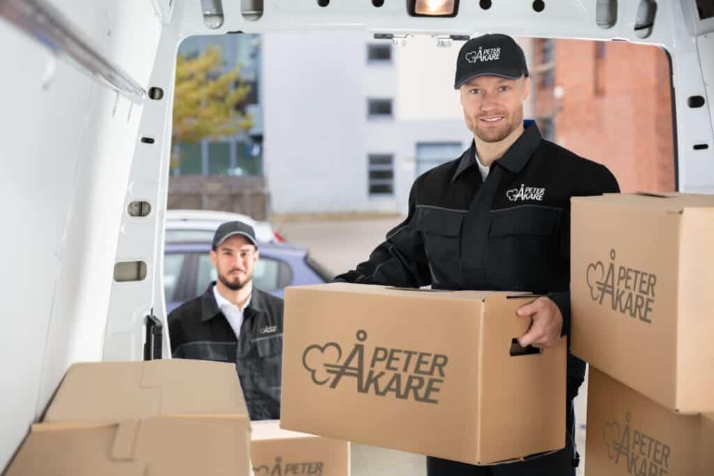 Två flyttarbetare från Flyttfirma Peter Åkare lastar in flyttkartonger i bil intill hus i Stockholm