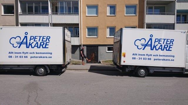 Två flyttbilar står uppställda utanför flerbostadshus