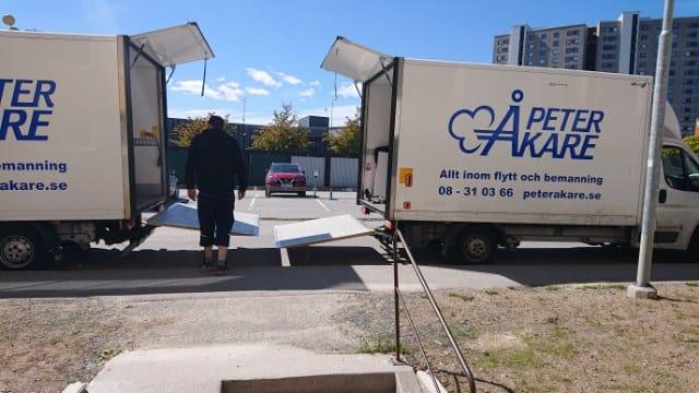 En person står mellan två öppna flyttbilar från Flyttfirma Peter Åkare AB