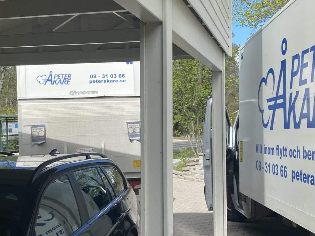 Två flyttbilar från flyttfirma Peter Åkare AB står vid hus.