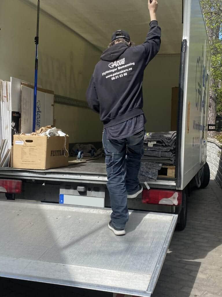 Flyttpersonal från flyttfirma Peter Åkare AB i lastutrymme på flyttbil.