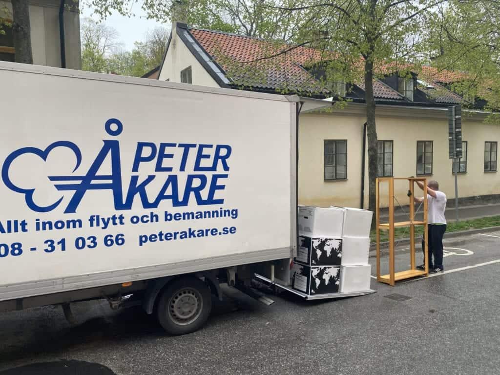 Lossning utanför 1700-talshus på Södermalm med flyttbil och flyttkartonger.