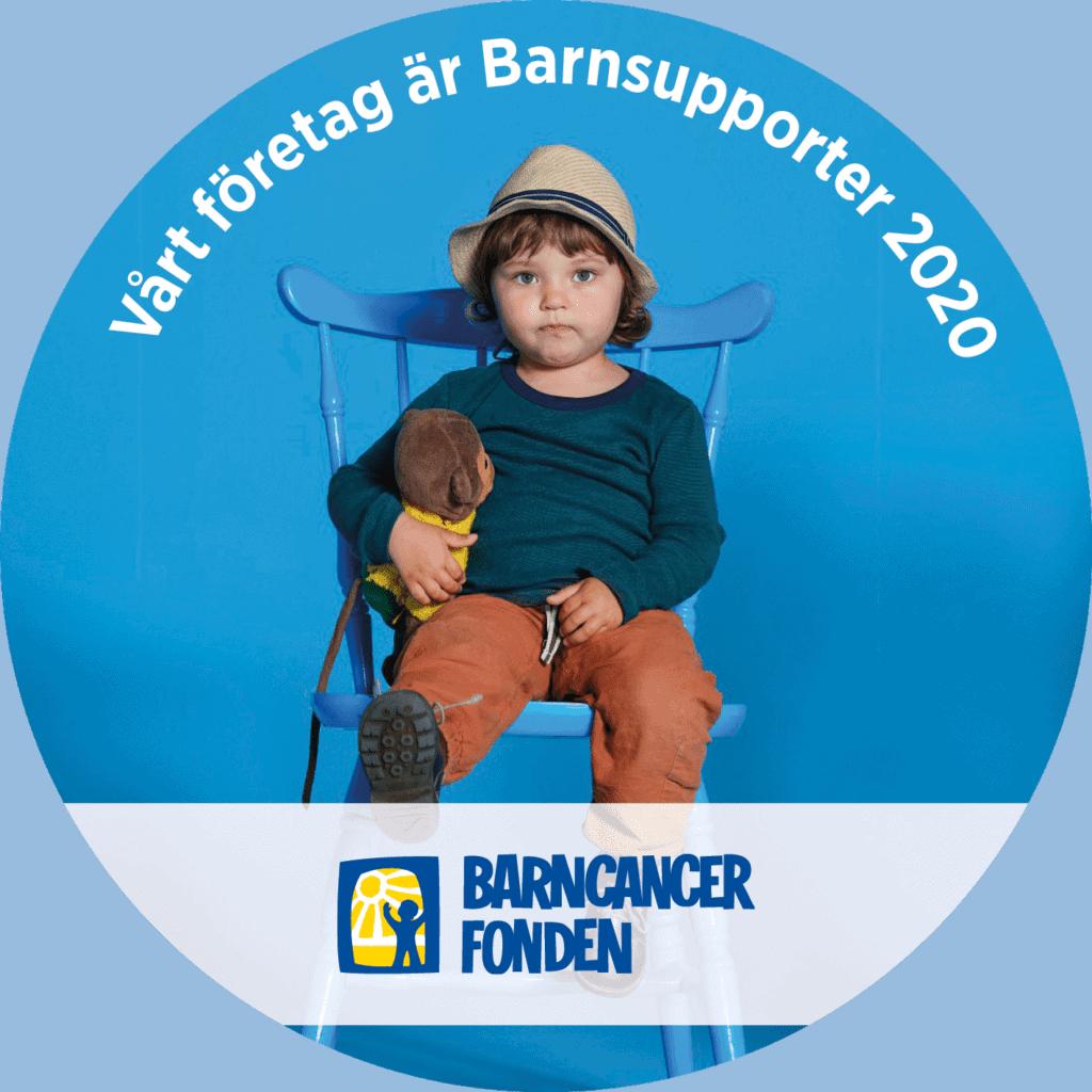 Barnsupportermärket - Barncancerfonden. På bilden syns ett barn sittandes på en stol med ett mjukisdjur i handen.