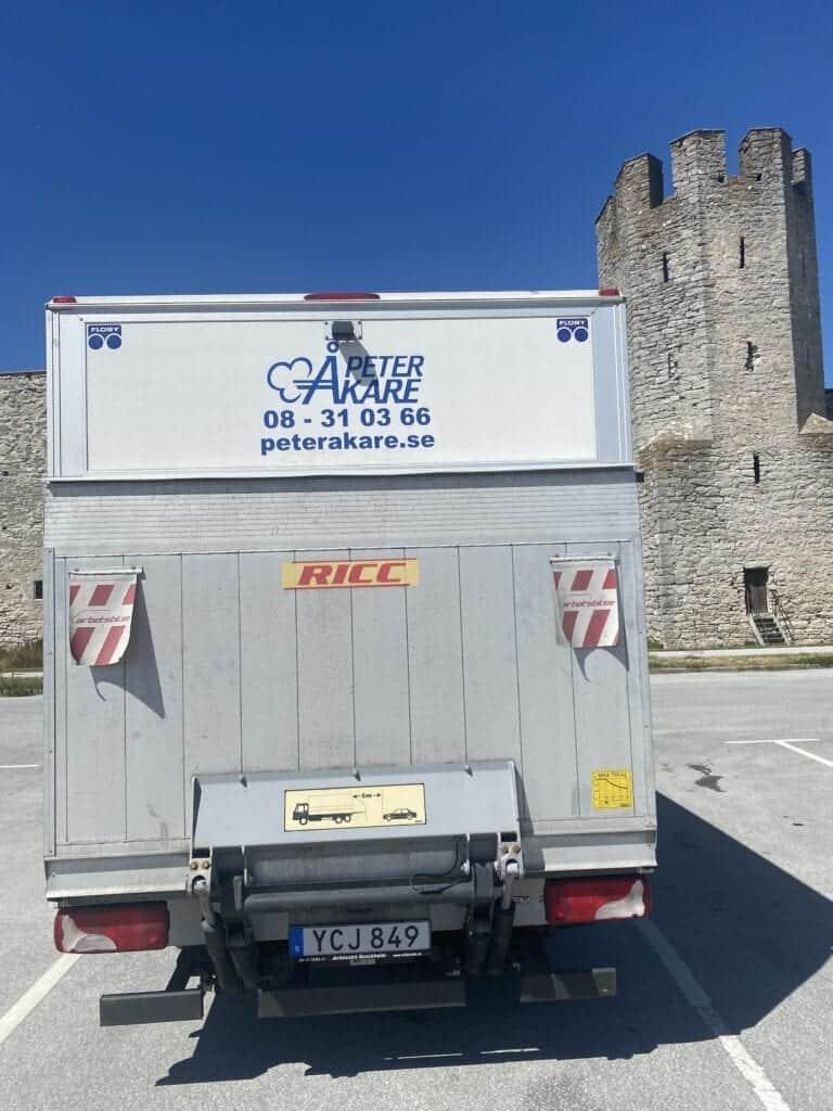 Vit flyttbil bakifrån från Flyttfirma Peter Åkare på Gotland under gotlandsflytt för en av våra kunder. I bakgrunden syns Ringmuren i Visby