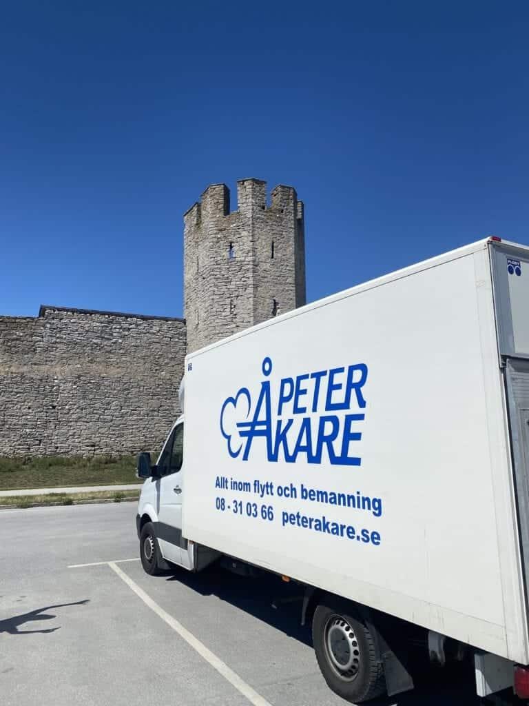 Vit flyttbil snett bakifrån från Flyttfirma Peter Åkare på Gotland under gotlandsflytt för en av våra kunder. I bakgrunden syns Ringmuren i Visby
