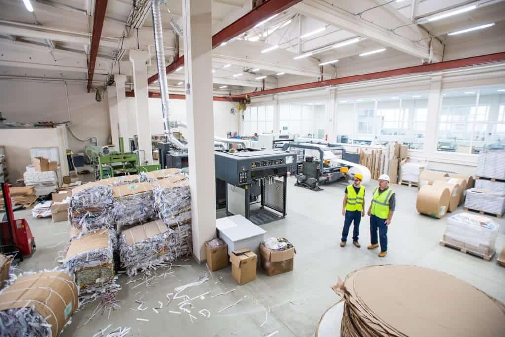 Två anställda inne på en stor återvinningsanläggning