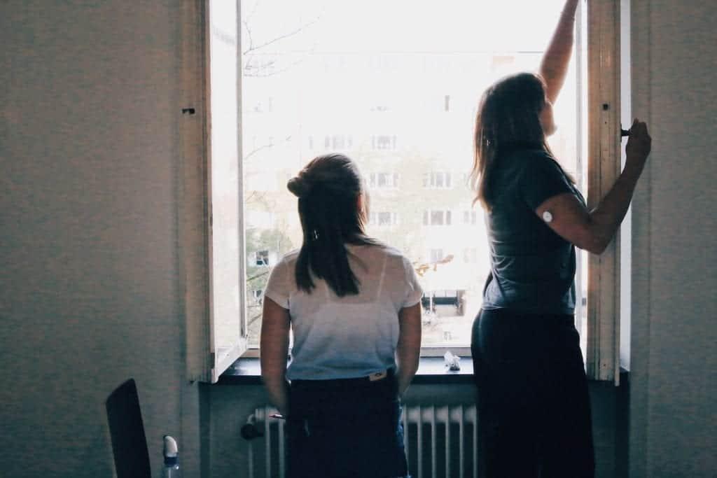 Två personer rengör fönster under flyttstädning