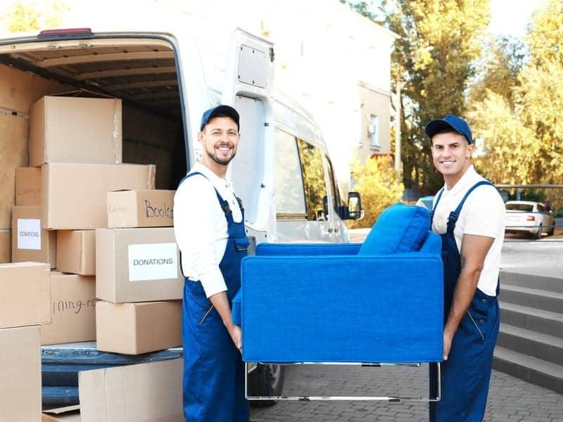 Två flyttarbetare bär en blå fåtölj intill flyttbil