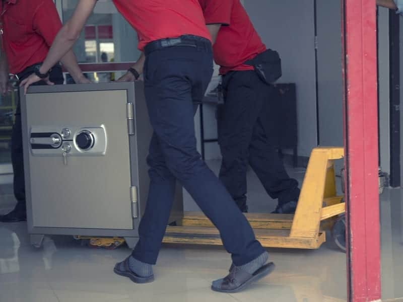 personer transporterar ett kassaskåp på rullvagn