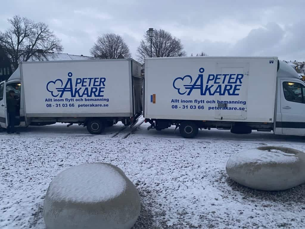 Två flyttbilar från Flyttfirma Peter Åkare AB uppställda utomhus med snövit bakgrund på Gotland