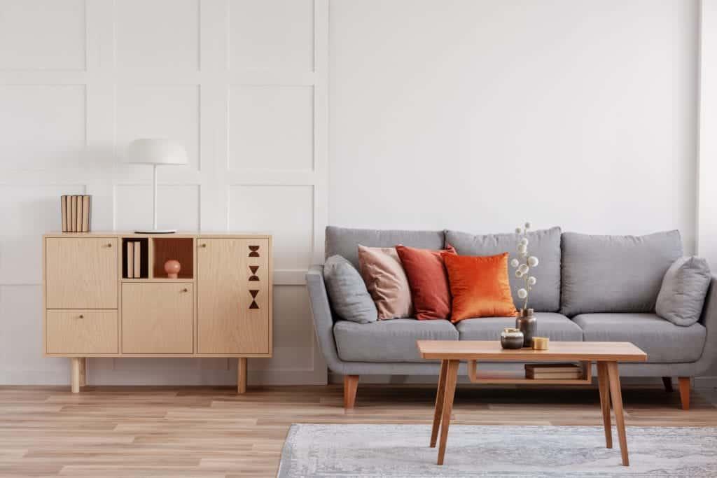 vardagsrum med grå soffa, soffbord i trä och förvaringsskåp intilll