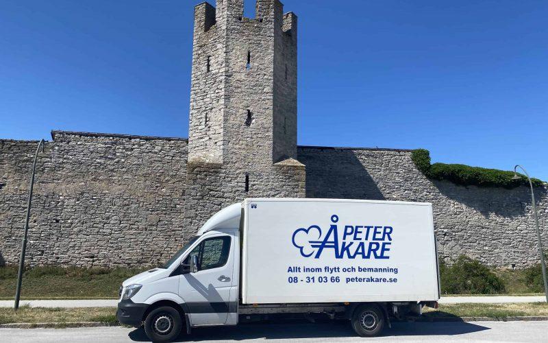 Vit flyttbil från Flyttfirma Peter Åkare på Gotland under gotlandsflytt för en av våra kunder. I bakgrunden syns Ringmuren i Visby