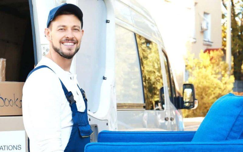 Två flyttarbetare bör en blå möbel intill flyttbil